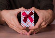 Due mani maschii nella forma di cuore che tiene il contenitore di regalo a quadretti con Fotografia Stock