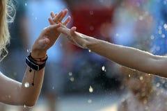 Due mani nelle gocce dell'acqua si uniscono Fotografie Stock Libere da Diritti