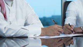 Due mani saudite degli uomini d'affari che firmano un documento Fotografie Stock Libere da Diritti