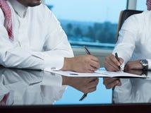 Due mani saudite degli uomini d'affari che firmano un Ducument Fotografie Stock