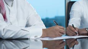 Due mani saudite degli uomini d'affari che firmano un Ducument Immagini Stock Libere da Diritti