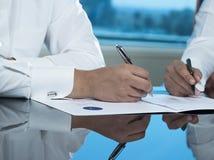 Due mani saudite degli uomini d'affari che firmano un Ducument Fotografie Stock Libere da Diritti