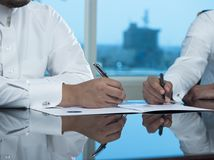 Due mani saudite degli uomini d'affari che firmano un Ducument Immagini Stock
