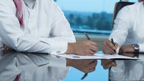 Due mani saudite degli uomini d'affari che firmano un Ducument Immagine Stock Libera da Diritti