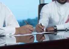 Due mani saudite degli uomini d'affari che firmano un Ducument Fotografia Stock Libera da Diritti