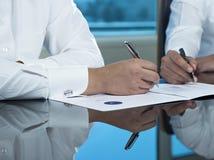 Due mani saudite degli uomini d'affari che firmano un Ducument Immagine Stock