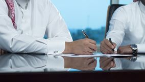 Due mani saudite degli uomini d'affari che firmano un Ducument Fotografia Stock