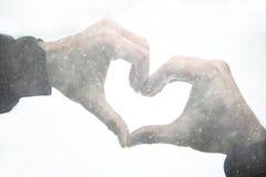Due mani si uniscono per formare una forma del cuore alle precipitazioni nevose Immagini Stock Libere da Diritti