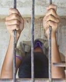 Due mani stanno afferrando la gabbia d'acciaio Fotografia Stock Libera da Diritti