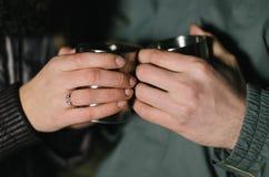 Due mani stanno tenendo due tazze Immagini Stock Libere da Diritti