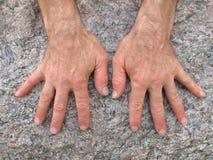 Due mani su una roccia immagine stock
