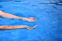 Due mani umane che prendono acqua su un fondo blu Fotografia Stock Libera da Diritti
