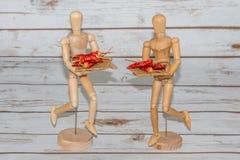 Due manichini di legno che serviscono peperoncino rosso Fotografia Stock