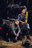 Due meccanici tatuati barbuti vicino all'automobile in un'officina Immagini Stock
