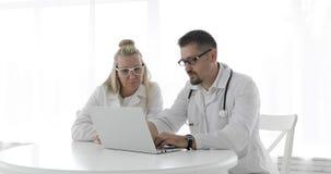 Due medici in abiti medici stanno sedendo ad una tavola bianca e stanno utilizzando un computer portatile video d archivio