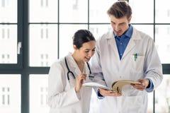 Due medici che controllano insieme la cartella sanitaria di un paziente fotografia stock