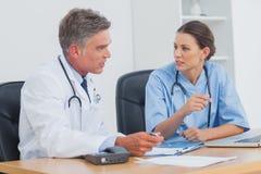 Due medici che discutono insieme e che lavorano Fotografia Stock