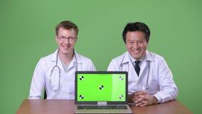 Due medici multi-etnici insieme contro fondo verde video d archivio