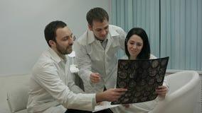 Due medici nel buon umore analizzano i risultati del paziente per diagnosticare la malattia, quindi viene interno con i raggi x fotografia stock