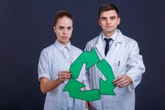 Due medici in uniforme di bianco, un tipo e una ragazza, supporto e tengono un segno, tre frecce verdi giranti Fotografia Stock