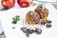 Due mele al forno in un piatto bianco su una tavola di legno immagine stock