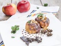 Due mele al forno in un piatto bianco su una tavola di legno immagine stock libera da diritti