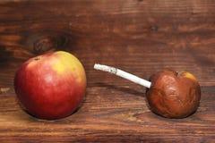 Due mele e una sigaretta nel fondo di legno Uccisioni del fumo Non fumatori Fotografia Stock Libera da Diritti