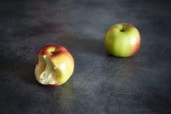 Due mele mature, una pungenti ed una intera su un fondo scuro Immagini Stock Libere da Diritti