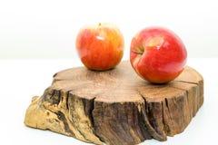 Due mele succose rosse si trovano su un ceppo di legno su fondo bianco Mele fresche su un ceppo di legno Frutta deliziosa e matur fotografie stock libere da diritti