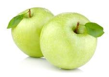 Due mele verdi con i fogli e le gocce di acqua Immagini Stock Libere da Diritti