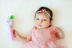 Due mesi di neonata sveglia con il crepitio Immagine Stock