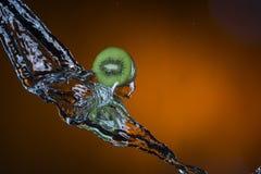 Due metà del kiwi e della spruzzata di acqua su fondo arancio Immagini Stock