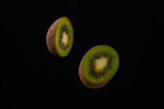 Due metà del kiwi e su fondo nero Fotografia Stock