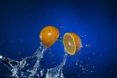 Due metà del limone e della spruzzata di acqua su fondo blu Immagine Stock