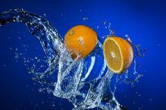 Due metà del limone e della spruzzata di acqua su fondo blu Fotografia Stock