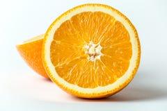 Due metà di frutta arancio fresca in un taglio su fondo bianco, alto vicino di macro Fotografia Stock