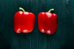Due metà di peperone dolce dolce rosso su una tavola di legno blu profonda scura Immagini Stock Libere da Diritti