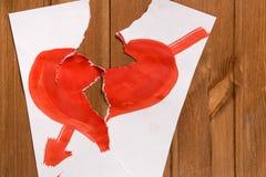 Due metà di un foglio di carta su cui la pittura rossa ha disegnato il cuore, Li Fotografia Stock