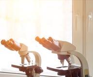 Due microscopi per esame stanno nel laboratorio sulla tavola, il sole, portata fotografia stock libera da diritti