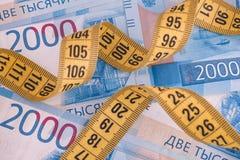 Due mila banconote della rublo e nastro di misurazione Immagine Stock