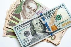 Due mila cinquecento hryvnia ucraini e cento dollari Immagine Stock Libera da Diritti
