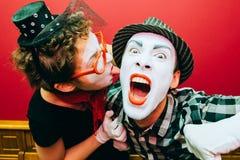 Due mimi che posano contro un fondo rosso della parete Fotografia Stock