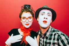Due mimi che posano contro un fondo rosso della parete Fotografia Stock Libera da Diritti
