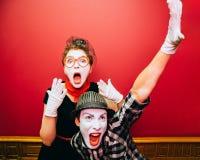 Due mimi che posano contro un fondo rosso della parete Fotografie Stock Libere da Diritti
