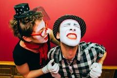 Due mimi che posano contro un fondo rosso della parete Immagine Stock
