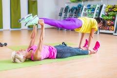 Due modelli femminili di forma fisica che fanno l'yoga si esercita, una che si trova sulle gambe della tenuta della stuoia del pa Fotografia Stock Libera da Diritti