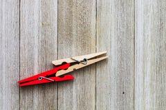 Due mollette da bucato, su rosso e sull'ordinario colorate su un backgro di legno Immagine Stock