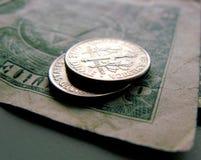 Due monete da dieci centesimi di dollaro su un dollaro Fotografia Stock