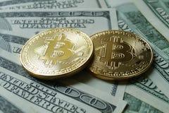 Due monete simboliche di bitcoin sulle banconote di cento dollari Immagine Stock Libera da Diritti