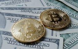 Due monete simboliche di bitcoin sulle banconote di cento dollari Fotografie Stock